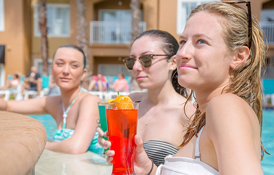 Women by the pool drinking cocktails at our Orlando Hotel